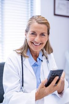 Retrato de médica usando telefone celular