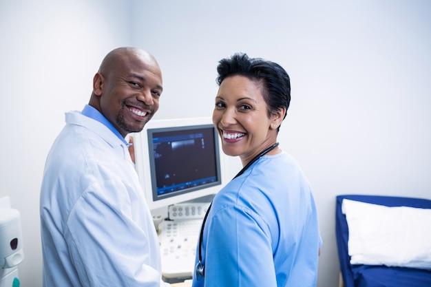 Retrato de médico e enfermeiro em pé perto da máquina de monitoramento de pacientes