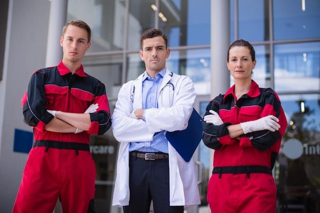 Retrato de médico e paramédico em pé com os braços cruzados