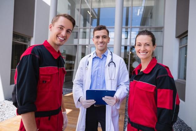 Retrato de médico e paramédico em pé no hospital