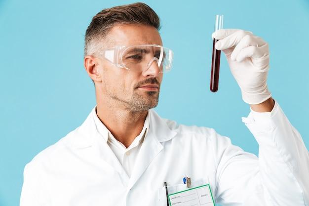 Retrato de médico especialista maduro usando óculos, segurando um tubo de ensaio com sangue, isolado na parede azul