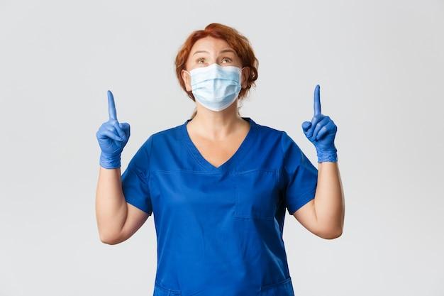 Retrato de médico feliz admirando algo para cima, enfermeira feminina com máscara facial e luvas olhando e apontando para cima com admiração