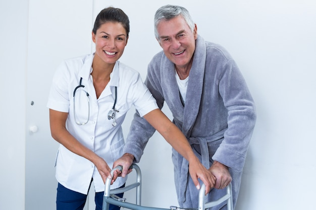Retrato, de, médico feminino, ajudando, homem sênior, andar, com, andador