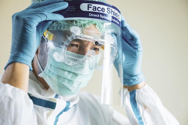 Retrato de médico feminino asiático vestindo protetor facial e terno de ppe para pacientes com coronavírus de tratamento.