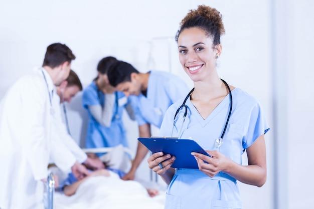 Retrato, de, médico feminino, segurando clipboard, e, sorrindo, enquanto, outro, doutor, examinando, um, paciente, atrás de, hospitalar