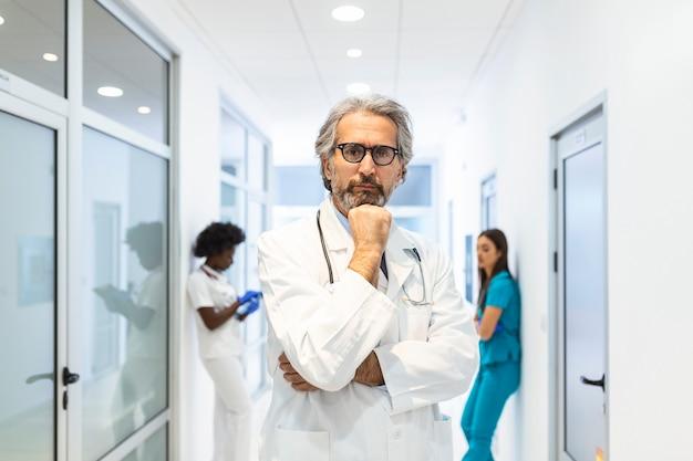 Retrato de médico masculino maduro, vestindo jaleco branco com estetoscópio no corredor do hospital movimentado.