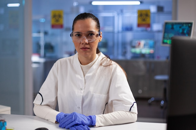 Retrato de médico mulher doutora sentada à mesa durante experimento de bioquímica