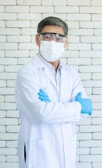 Retrato de médico ou pesquisador mais velho asiático usa jaleco, óculos transparentes e máscara facial em pé e o braço cruzado com fundo de tijolo branco.