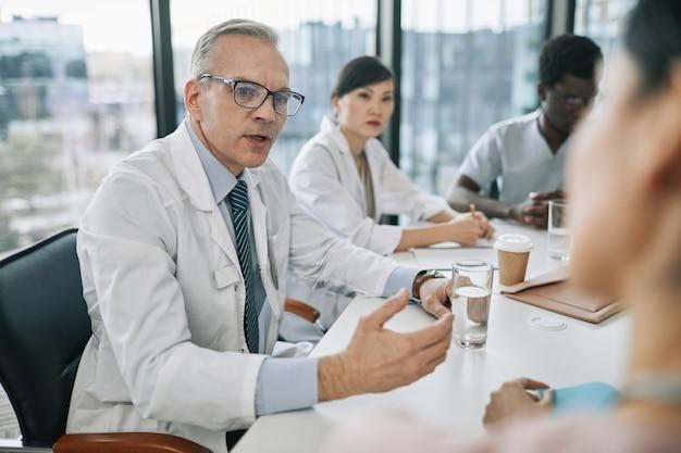 Retrato de médico sênior de cabelos brancos conversando com colegas na mesa de reunião durante conferência médica