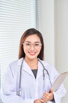 Retrato de médico sorridente em pé posando em seu escritório no hospital., conceito de ocupação médica e de saúde.