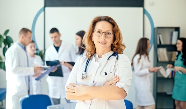 Retrato de médico sorridente satisfeito com seu trabalho em um hospital de saúde. profissionais médicos no trabalho. médica pediatra de jaleco branco com estetoscópio no pescoço.