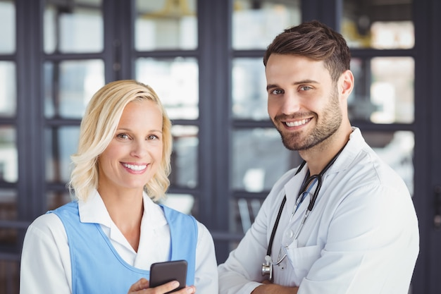Retrato de médicos sorridentes usando telefone celular