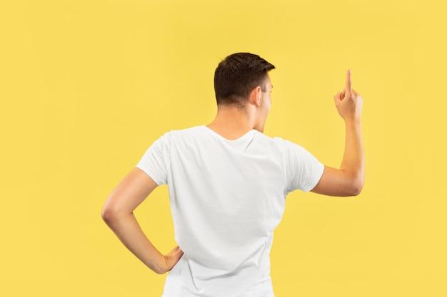 Retrato de meio comprimento de jovem caucasiano sobre fundo amarelo do estúdio. lindo modelo masculino na camisa. conceito de emoções humanas, expressão facial, vendas, anúncio. mostrando e apontando algo.