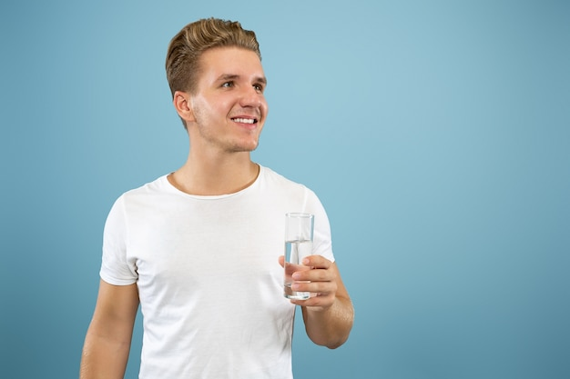 Retrato de meio comprimento de jovem caucasiano sobre fundo azul do estúdio. lindo modelo masculino na camisa. conceito de emoções humanas, expressão facial, vendas, anúncio. gostando de beber água pura.