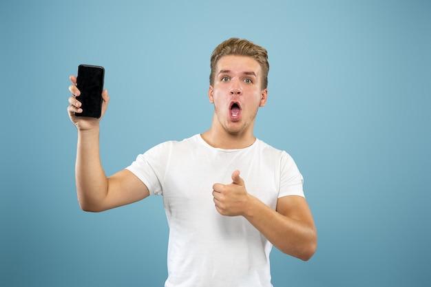 Retrato de meio comprimento de jovem caucasiano sobre fundo azul do estúdio. lindo modelo masculino na camisa. conceito de emoções humanas, expressão facial, vendas, anúncio. mostrando a tela do telefone, pagamento, apostas.