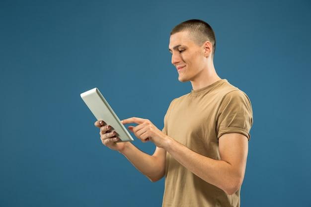 Retrato de meio comprimento de jovem caucasiano sobre fundo azul do estúdio. lindo modelo masculino na camisa. conceito de emoções humanas, expressão facial, vendas, anúncio. usando o tablet para selfie, vlog ou estudo.