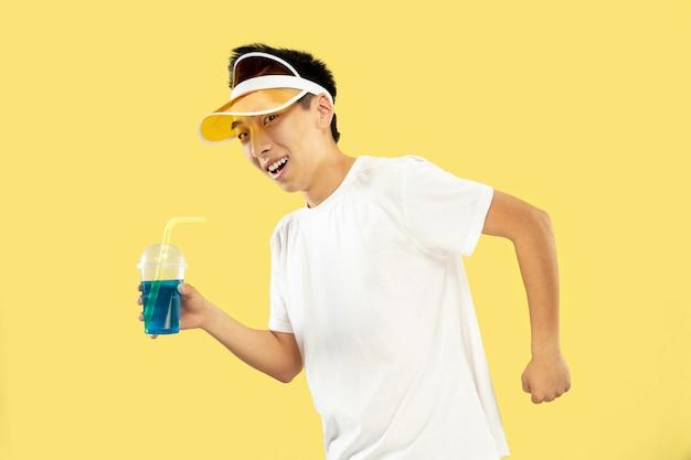 Retrato de meio comprimento de jovem coreano em fundo amarelo do estúdio. modelo masculino de camisa branca e boné amarelo. beber coquetel. conceito de emoções humanas, expressão, verão, férias, fim de semana.