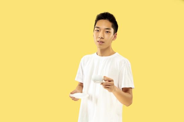 Retrato de meio comprimento de jovem coreano em fundo amarelo do estúdio. modelo masculino em camisa branca. tomando café, sentindo-se feliz. conceito de emoções humanas, expressão facial. vista frontal. cores da moda.