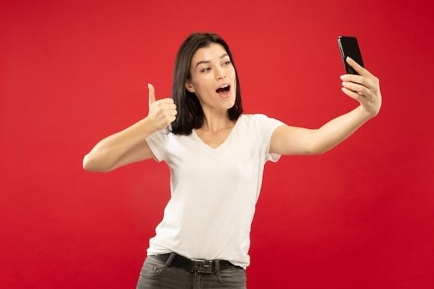 Retrato de meio comprimento de mulher jovem caucasiana em fundo vermelho studio. bela modelo feminino em camisa branca. conceito de emoções humanas, expressão facial. fazendo selfie ou seu próprio vlog, blog.
