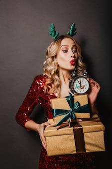 Retrato de meio comprimento de uma adolescente loira encaracolada com presentes