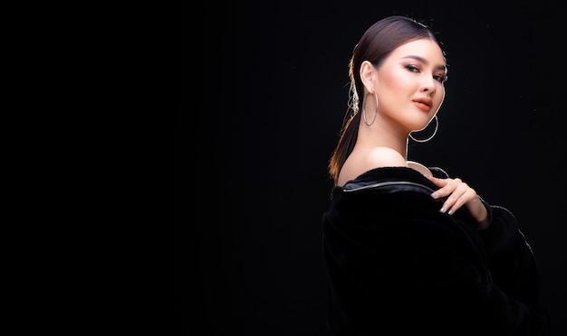 Retrato de meio corpo de 20 mulher asiática em estilo de jaqueta preta de alta moda sobre fundo preto com iluminação de fundo, copie o espaço