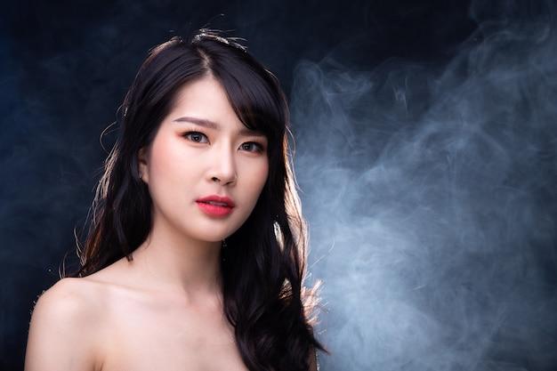 Retrato de meio corpo de 20 mulheres asiáticas em estilo de alta moda sobre fundo de névoa de fumaça com iluminação de fundo, copie o espaço