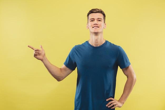 Retrato de meio corpo de jovem caucasiano em estúdio amarelo