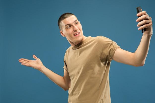 Retrato de meio corpo de jovem caucasiano em estúdio azul