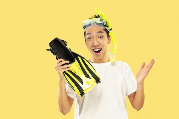 Retrato de meio corpo de jovem coreano na parede amarela