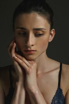 Retrato de meio corpo de jovem triste em roupa interior na parede escura do estúdio
