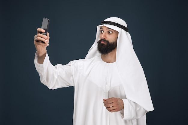 Retrato de meio corpo de um homem árabe em estúdio azul escuro