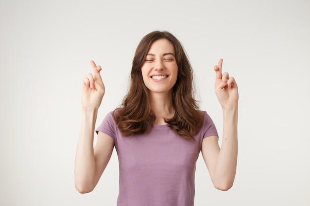 Retrato de meio corpo de uma linda mulher sonhadora, com o corpo relaxado, cruzando os dedos com os olhos fechados
