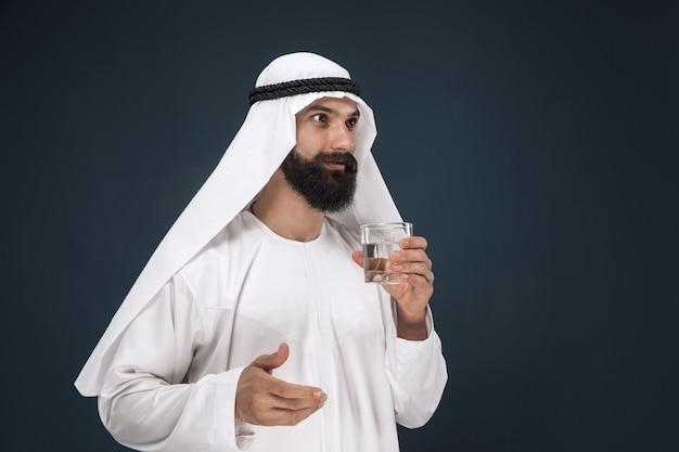 Retrato de meio corpo do empresário saudita árabe em estúdio azul escuro
