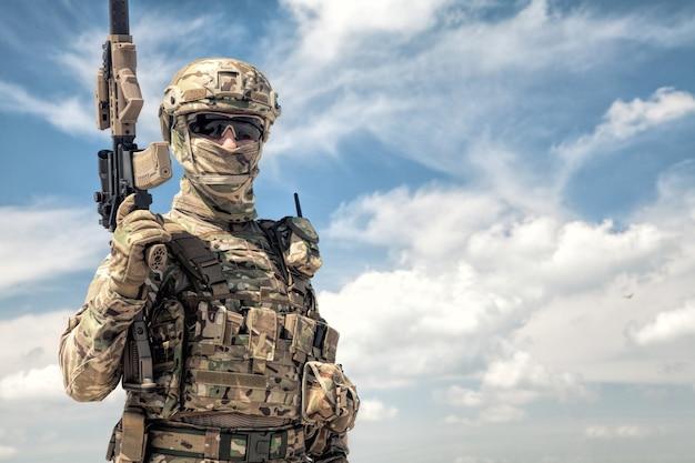 Retrato de meio corpo do jogador de airsoft em uniforme de camuflagem do exército, capacete tático, carregador de carga e rosto escondido atrás da máscara, posando com uma réplica de arma de fogo nas mãos, céu nublado no fundo