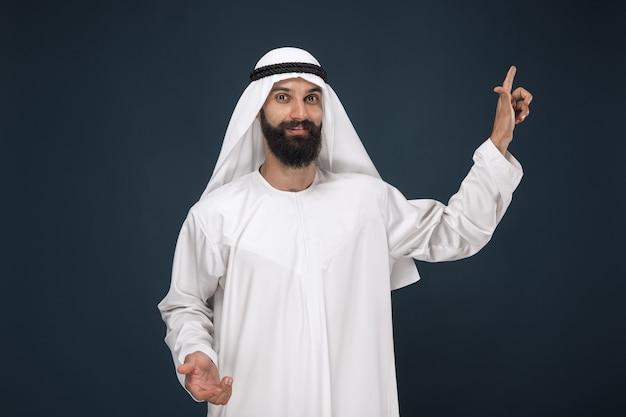 Retrato de meio corpo do saudita árabe em estúdio azul escuro