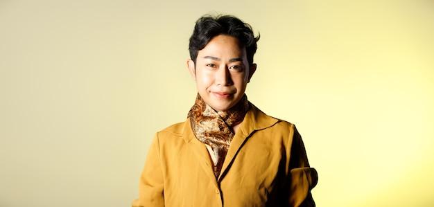 Retrato de meio corpo dos anos 20 asiático lgbtqia + cabelo preto de homem gay usa camisa amarela com lenço. homem da moda posa meio corpo sobre fundo bege