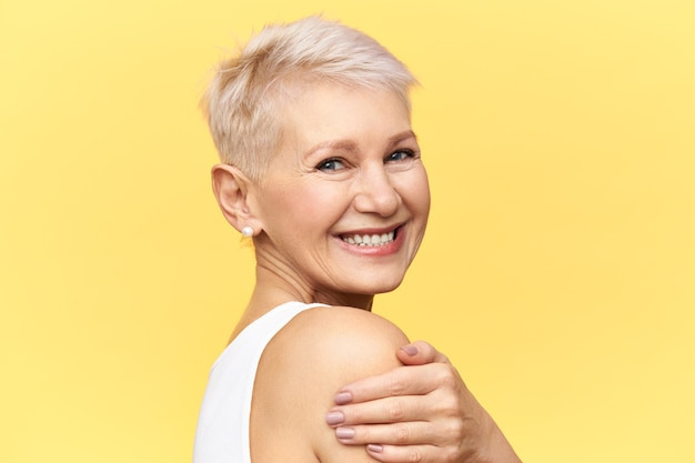 Retrato de meio perfil de alegre feliz linda aposentada se divertindo, posando isolada, abraçando-se, olhando para a câmera com um sorriso alegre