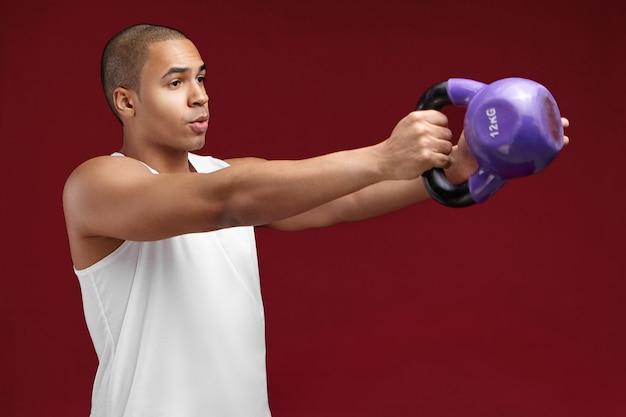 Retrato de meio perfil de jovem fisiculturista de pele escura e cabeça raspada, exercitando-se com halteres. esportista africano musculoso malhando com muito peso, fortalecendo os músculos dos braços