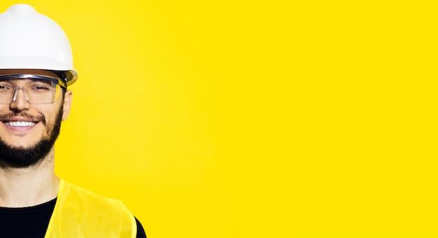 Retrato de meio rosto de jovem sorridente, engenheiro de construção, trabalhador, usando capacete de segurança e óculos de proteção amarelos