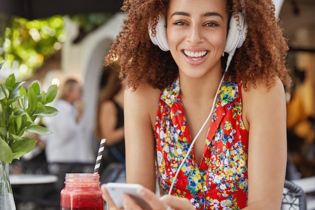 Retrato de melomana africana sorridente positiva aprecia música popular, conectada a um smartphone e fones de ouvido, bebe smoothie