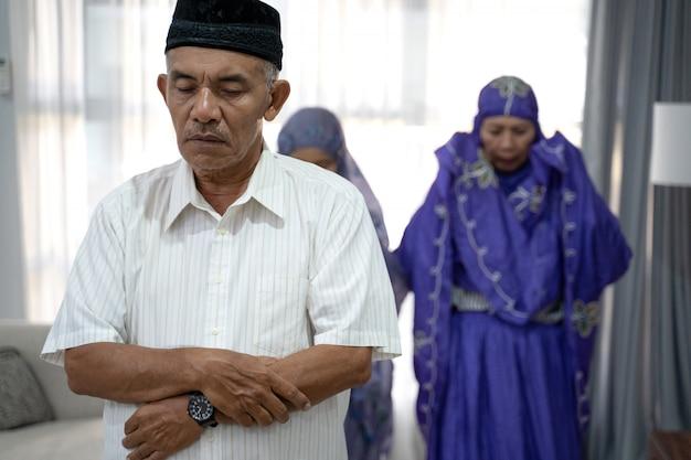Retrato de membros da família rezando em congregação na sala de oração