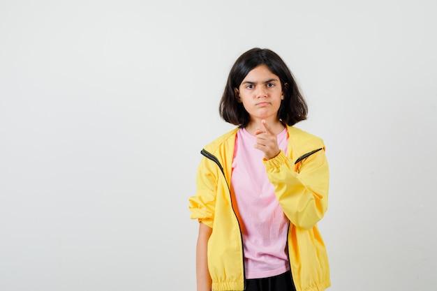 Retrato de menina adolescente advertindo com o dedo na camiseta, jaqueta e olhando com raiva vista frontal