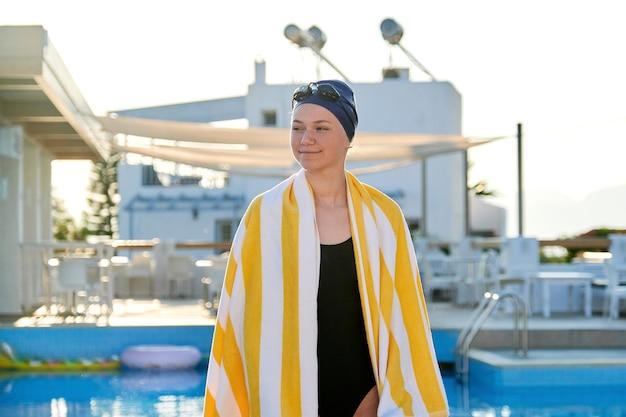 Retrato de menina adolescente ativa em maiô esportivo, chapéu com toalha nos ombros, fundo de piscina ao ar livre Foto Premium