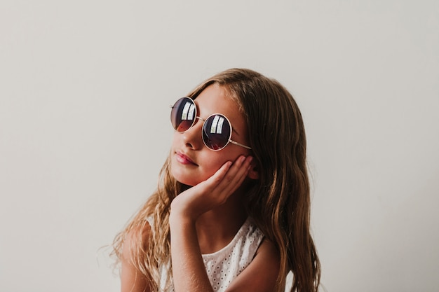 Retrato de menina adolescente bonita em casa. sentado e usando óculos de sol modernos. conceito de felicidade e estilo de vida