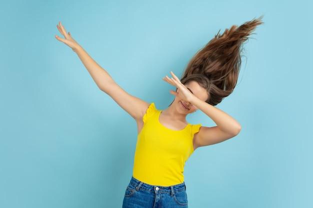 Retrato de menina adolescente branca isolado na parede azul do estúdio