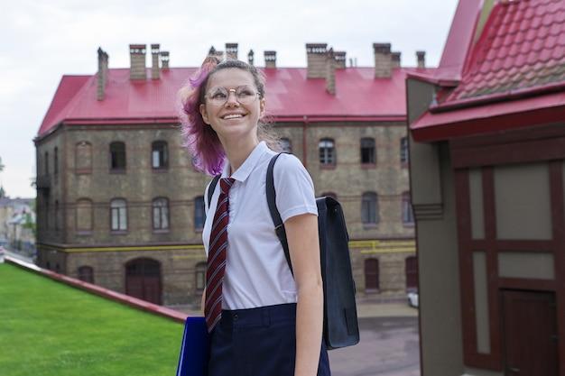 Retrato de menina adolescente com mochila para a escola, manhã de outono de verão, plano de fundo do prédio da escola. de volta à escola, de volta à faculdade