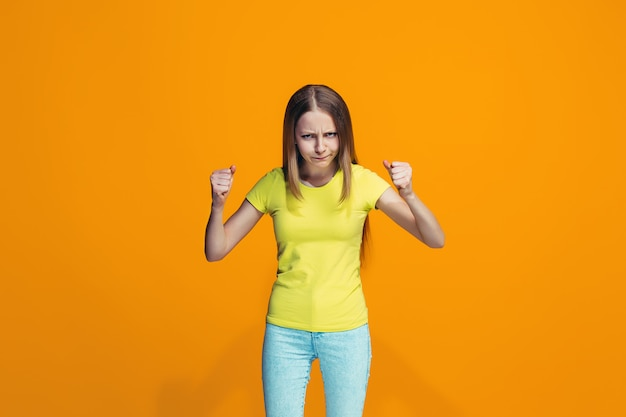 Retrato de menina adolescente com raiva em uma parede laranja