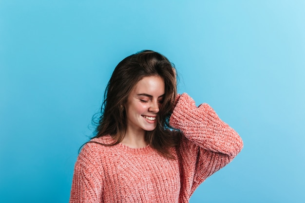 Retrato de menina adolescente de suéter rosa. modelo sorri com os olhos fechados na parede azul.