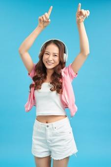 Retrato de menina adolescente feliz sorridente no fundo da parede azul. estilo adolescente de beleza.