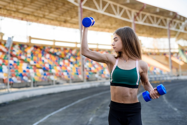 Retrato de menina adolescente fitness fazendo exercício com halteres no estádio da cidade. .